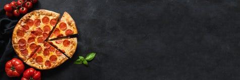 鲜美辣香肠烘饼和烹调成份蕃茄,香料,在黑具体背景的蓬蒿 库存图片