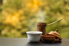 鲜美通入蒸汽的咖啡在传统土耳其咖啡罐,咖啡馆桌酿造了外面 免版税库存照片