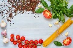 鲜美面团的成份:未加工的西红柿,蓬蒿,大蒜,在灰色具体厨房用桌上的胡椒与文本的空间 免版税库存照片