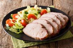 鲜美食物:与新鲜蔬菜关闭u的切的猪里脊肉 免版税图库摄影