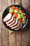 鲜美食物:与新鲜蔬菜关闭u的切的猪里脊肉 免版税库存图片