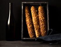鲜美食物 法国酥脆长方形宝石和瓶在黑色的酒 免版税库存照片