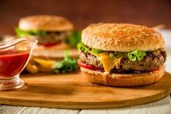 鲜美经典汉堡包用牛肉和西红柿酱在木板材 在倾吐的餐馆沙拉的主厨概念食物新鲜的厨房油橄榄 免版税库存图片