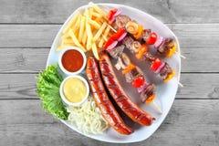 鲜美Kebabs、香肠、油炸物和素食者在板材 库存图片