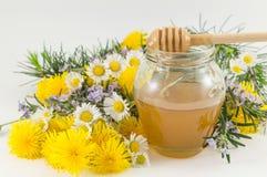 鲜花和一个瓶子蜂蜜 库存图片