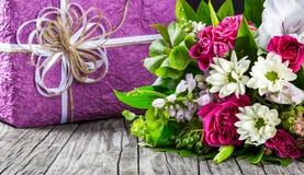 鲜花和礼物盒花束在一张老木桌上 免版税库存图片