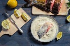 鲜鱼、作为成份的面粉和柠檬在盘 库存图片