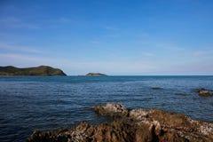 鲜绿色海和蓝天和岩石 库存照片