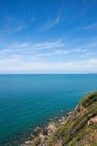 鲜绿色海和蓝天和岩石 免版税图库摄影