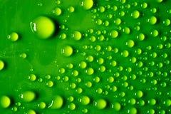 鲜绿色的塑料表面上的很多透明水滴,以抓痕 宏指令 库存照片