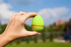 鲜绿色的美丽的复活节彩蛋在手中  免版税库存图片