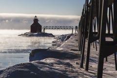 鲟鱼在有雾的黎明的海湾灯塔 免版税库存图片