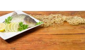 鲤鱼为烹调在木板条的盘做准备 免版税库存图片