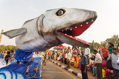 鲨鱼巨型雕塑在惊吓传统果阿狂欢节的人群的一个流动平台的人 库存照片