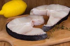 鲨鱼牛排用在一块砧板的柠檬 图库摄影