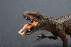 鲨齿龙玩具抓住更小的恐龙关闭 库存图片