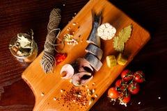 鲱鱼片断在一个切板的,在胡椒旁边,大蒜,在分支的蕃茄,荷兰芹,酱瓜 免版税库存照片