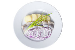 鲱鱼片断用土豆,在a的红洋葱 免版税库存图片