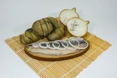 鲱鱼用葱和土豆 免版税库存图片
