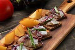 鲱鱼用被烘烤的土豆和葱在盘子在木背景 免版税库存图片