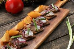 鲱鱼用被烘烤的土豆和葱在盘子在木背景 库存照片