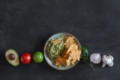 鳄梨调味酱捣碎的鳄梨酱板材与玉米片和成份的 免版税库存照片