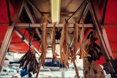 鳕鱼在卑尔根在鱼海边市场上被烘干, Bakalau垂悬在一条绳索 图库摄影