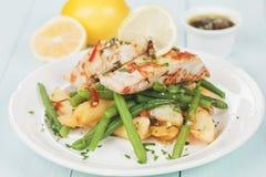 鳕鱼牛排用油煎的土豆和青豆 免版税库存照片