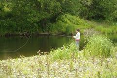 鳟鱼的年轻男孩用假蝇钓鱼 免版税图库摄影