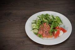 鳟鱼肉在一块板材的有菜和葡萄柚的 库存图片