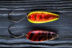 鳟鱼诱饵 在黑木背景的用作鱼饵的微曲金属片 图库摄影