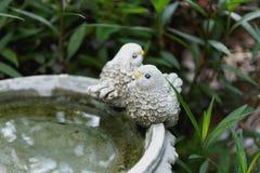 鸟玩偶装饰夫妇雕象在庭院里 免版税图库摄影