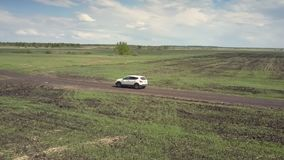 鸟瞰图不尽的领域和白色汽车在地面路 股票视频
