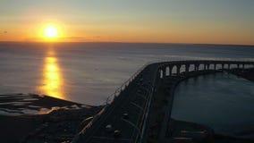 鸟瞰图在继续前进高速公路桥梁的海和汽车的晚上日落在城市 股票录像