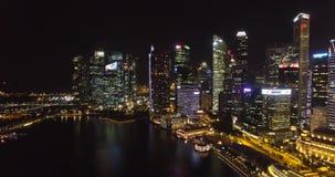 鸟瞰图新加坡摩天大楼在晚上 飞行在新加坡` s商业区上 股票录像