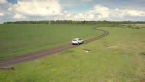 鸟瞰图沿蜿蜒在领域中的路的汽车驱动 股票录像