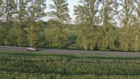 乡村道路上灰色轿车驾驶的航空观 侧视图跟踪快照 4K 股票录像