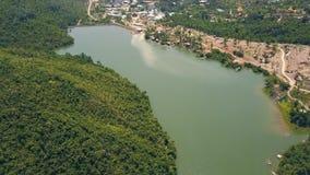 鸟瞰图绿色湖和水坝在背景小山和山盖了ropical森林飞行寄生虫在河与 影视素材