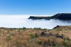 鸟瞰图马德拉岛山形式上面与云层的在海洋 免版税库存图片