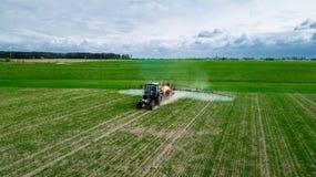 鸟瞰图,在大豆豆领域的拖拉机喷洒的杀虫剂 免版税库存照片