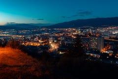 鸟瞰图,夜与夜空的都市风景视图 与烟花的自然清晰视界在与路灯到底的大街区和 免版税库存图片