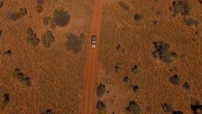 鸟瞰图:与旅行在纳米比亚的大草原的路的人的suv 股票视频