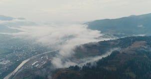 鸟瞰图:有薄雾的森林,飞行通过云彩在Transcarpathian城市Mizhgirja 影视素材