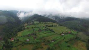 鸟瞰图 在山willarge的飞行在美丽的云彩 空中摄影机射击 航空云彩 雾 蒸汽 股票录像