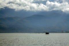鸟群在湖的有在距离的一条小船的 库存照片