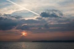 鸟群飞行在有日出的湖Leman在的云彩后 库存图片
