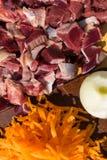 鸟鸡内脏杂碎胗胃、心脏用葱和红萝卜 未加工的未煮过的鸡火鸡胗背景 免版税库存照片