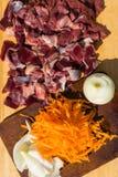 鸟鸡内脏杂碎胗胃、心脏用葱和红萝卜 未加工的未煮过的鸡火鸡胗背景 图库摄影