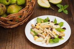 鸡丁沙拉,梨,烘干了鹅莓,并且无核小葡萄干,在蓬蒿的乳酪离开 木背景 顶视图 特写镜头 免版税库存图片