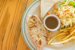 鸡与法语的牛排服务油煎了沙拉和面包 免版税库存图片